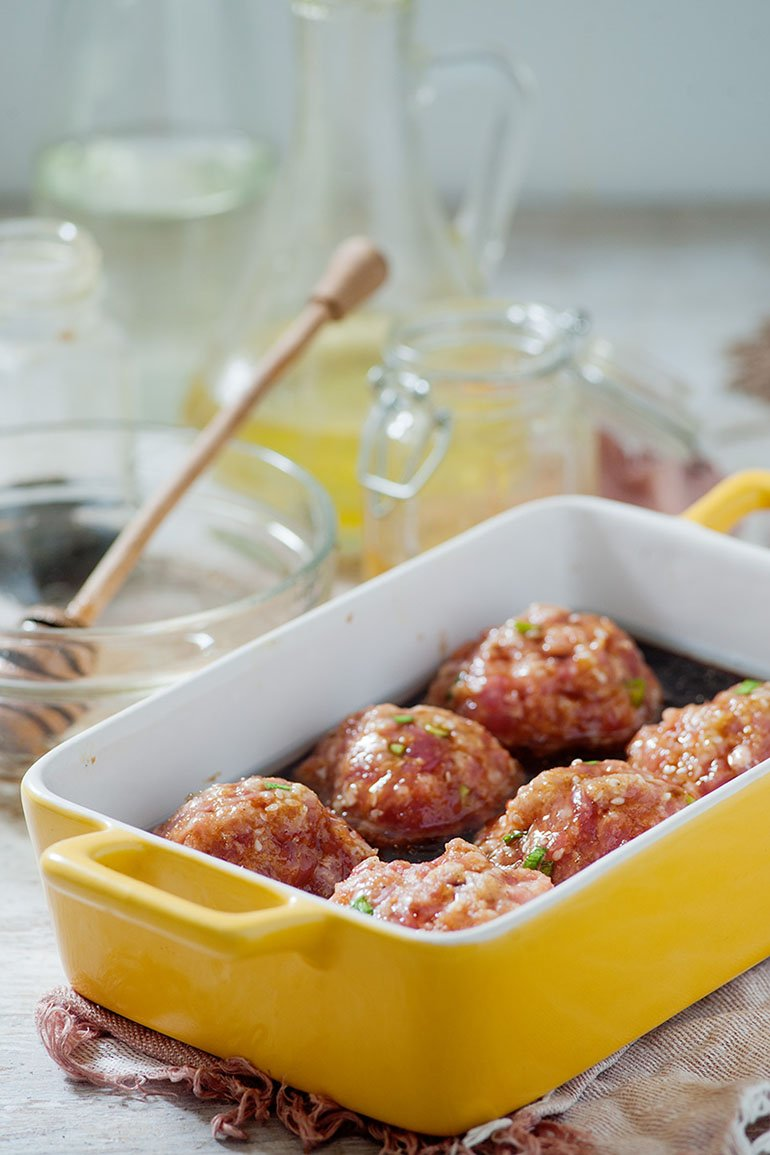 asian honey ginger meatballs sitting in tray with honey sauce