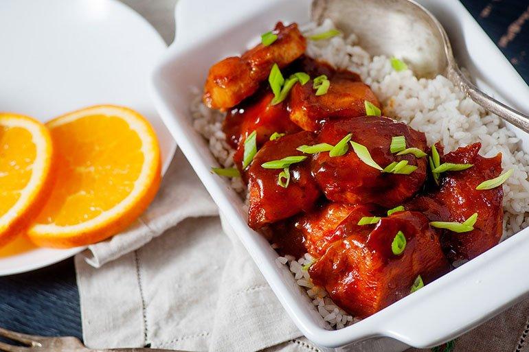 Chicken with garnish and orange presented on kitchen table