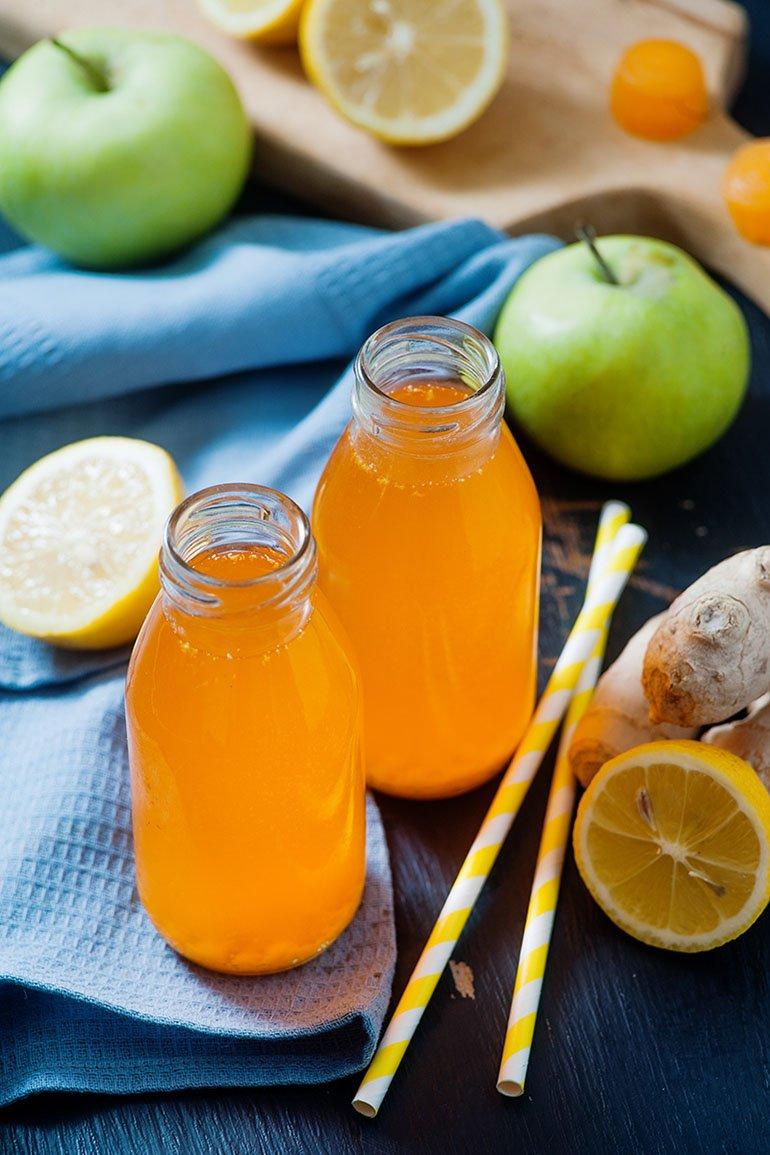 turmeric drink on table with straws and lemons