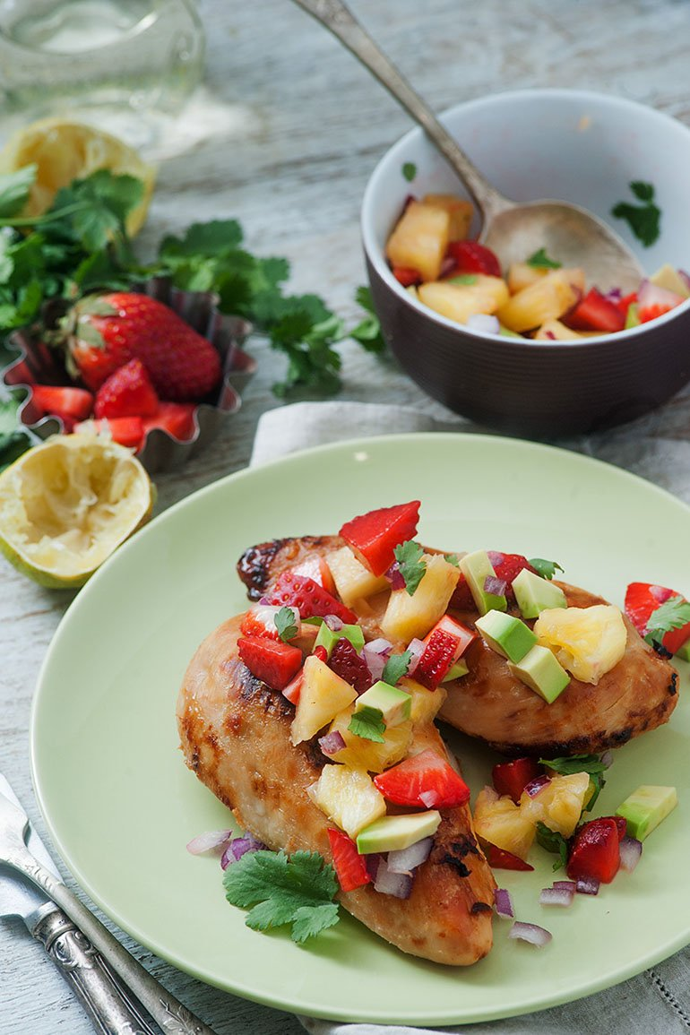 chicken fresh off the grill with generous serving of pineapple and avocado salsa placed on top