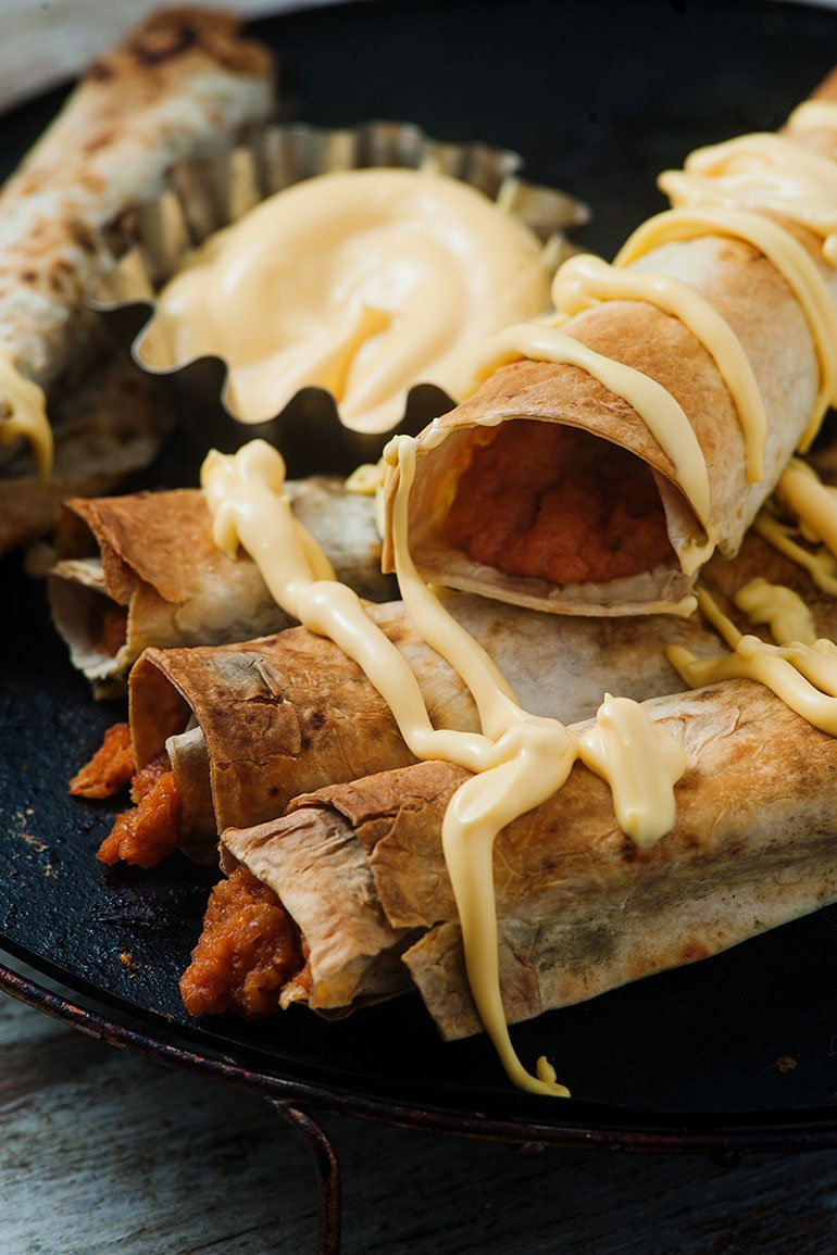 vegan baked buffalo chickpea taquitos with vegan cheese sauce