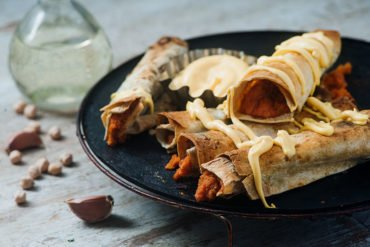 vegan baked buffalo chickpea taquitos with vegan cheese sauce served on plate