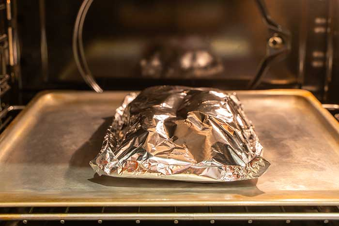 Food covered with foil on the pan inside gas oven ready for cooking