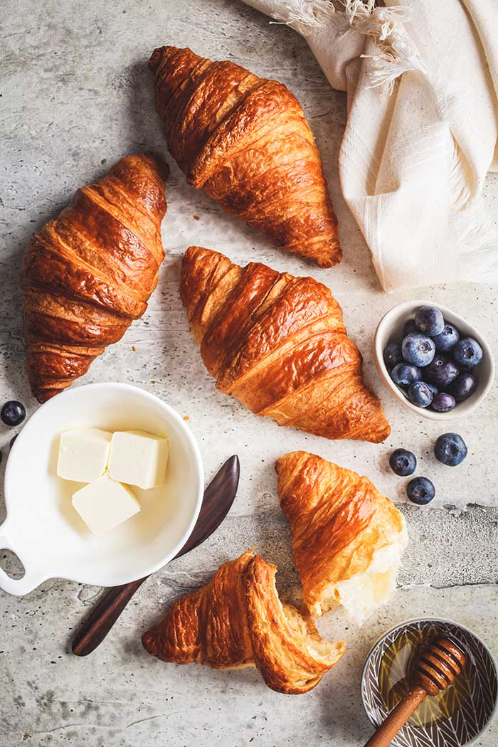 Fresh croissants with blueberries and honey