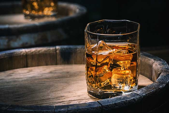 Glass of Scotch whiskey and ice sits on top of a rustic whiskey barrel