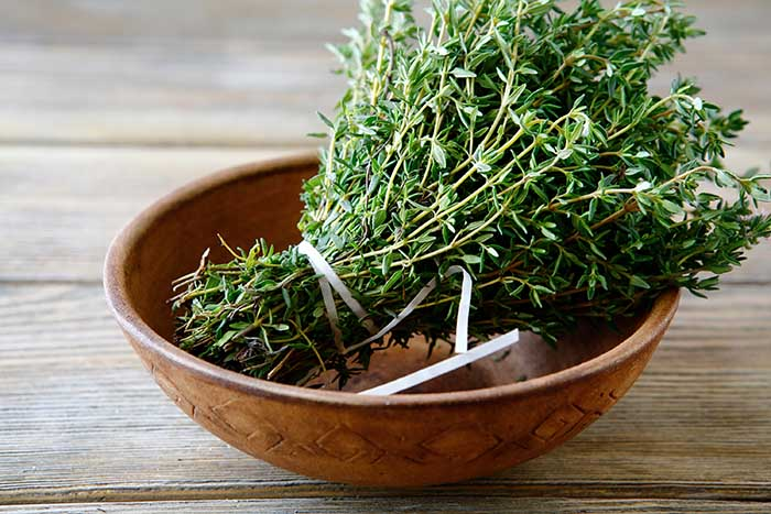Green thyme in a bowl on boards
