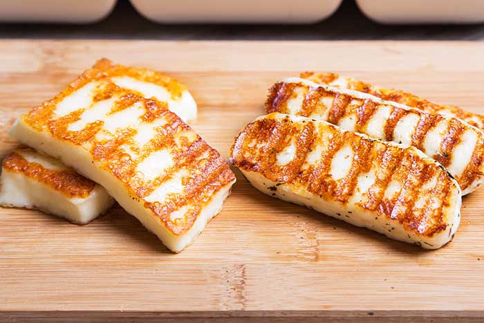 Grilled haloumi cheese on a wooden board