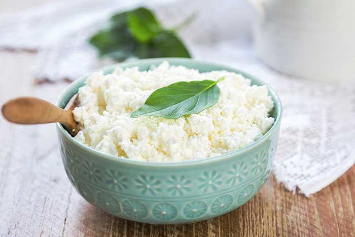 Homemade Ricotta cheese by a jug of milk