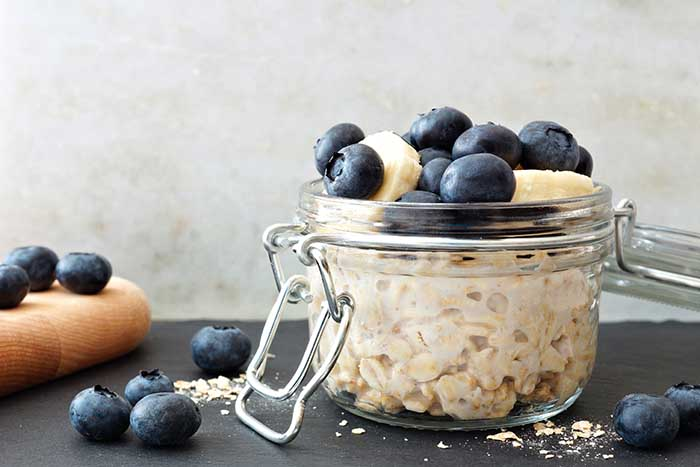 Overnight oats with fresh blueberries and bananas in jars