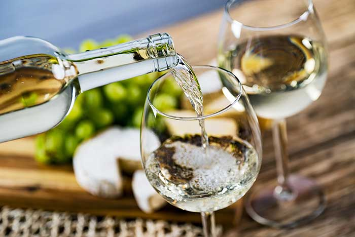 Pouring white wine into the glass against wooden table