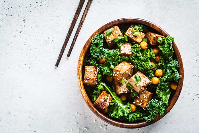 Teriyaki tofu salad with kale and chickpeas in wooden bowl