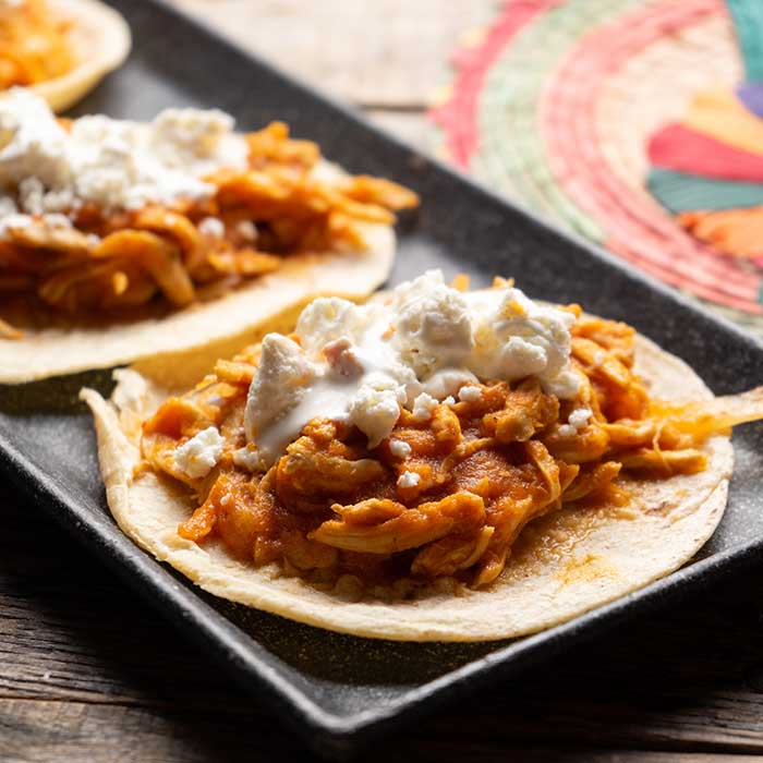 Traditional mexican chicken tinga tacos with chipotle sauce