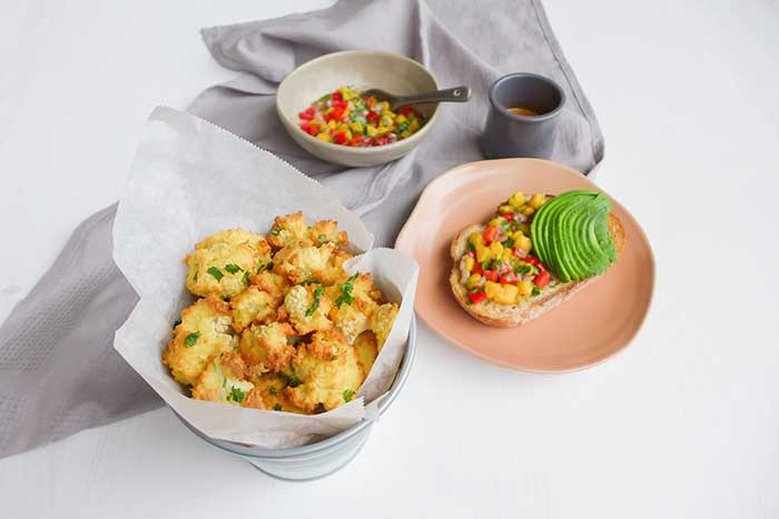bang bang cauliflower served in basket besides pineapple salsa on toast