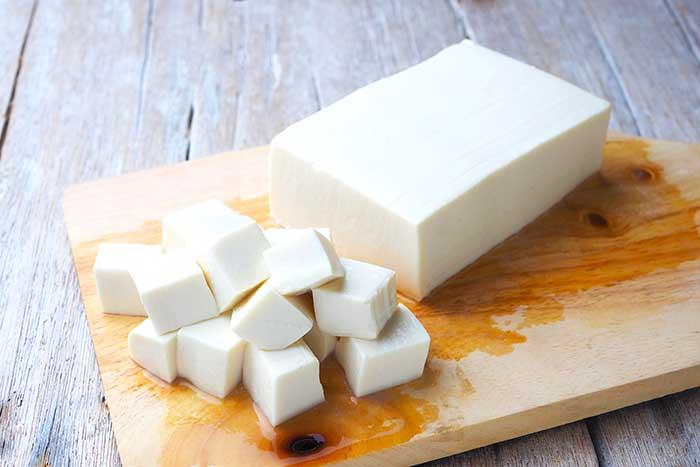 diced soft tofu on a cutting boar
