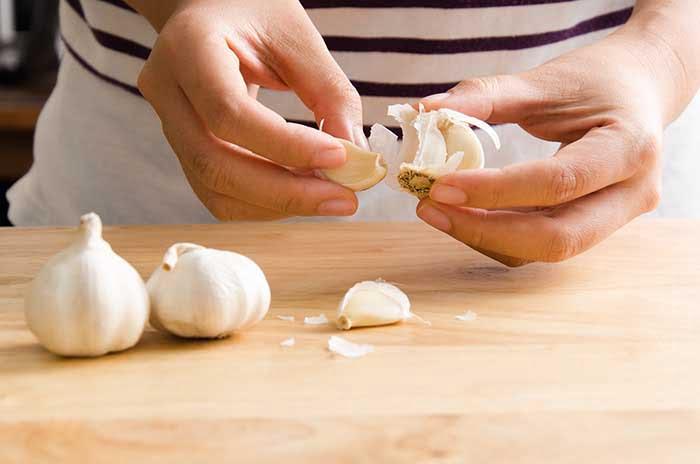 chef peeling garlic for paste recipe
