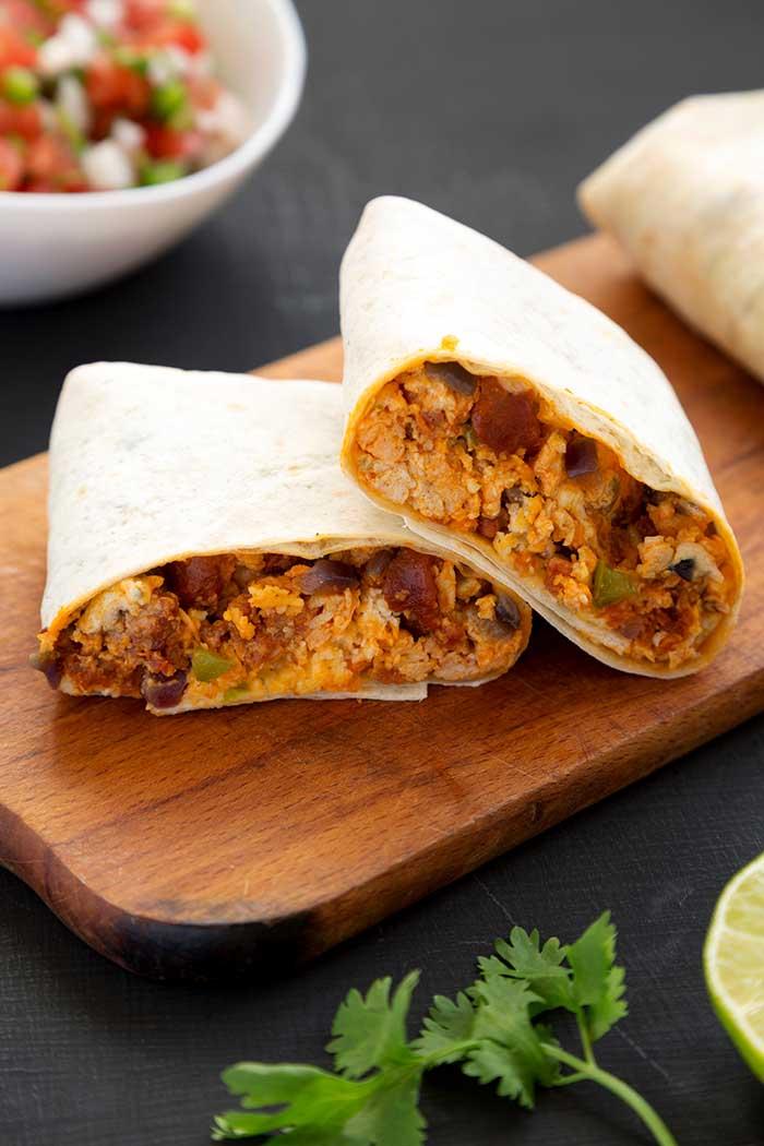 chorizo egg breakfast burrito served on wooden kitchen serving board