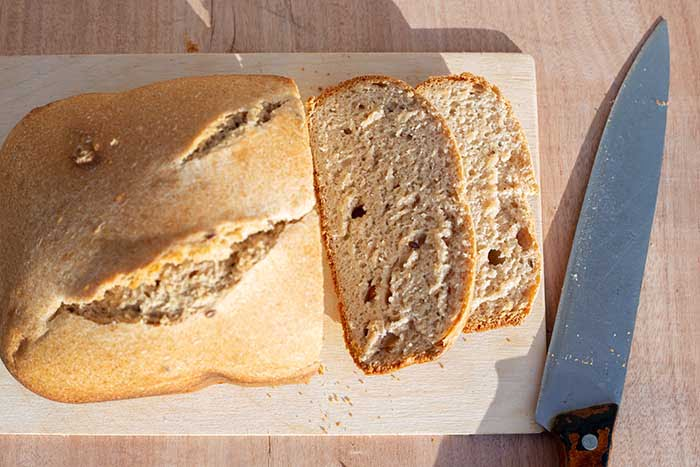 homemade whole grain bread with flax seeds freshly baked in a bread maker. Sliced slices on a cutting board.