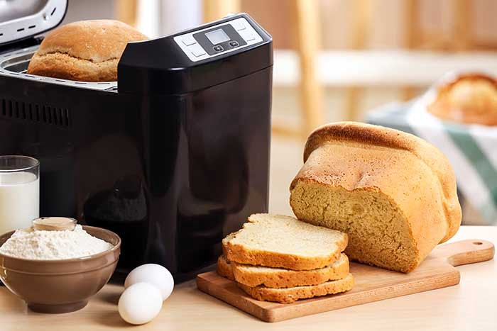 Tasty sliced loaf and bread machine on table