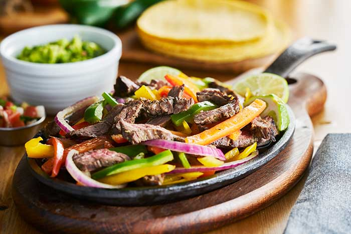 mexican beef fajitas in iron skillet with bell peppers and guacamole on the side