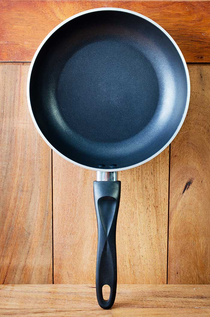 nonstick iron frying pan on wooden kitchen surface