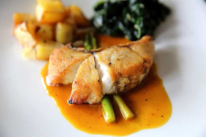chilean sea bass fillet steak with potatoes and spinach in lemon sauce