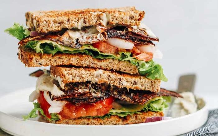 plant-based sandwich containing fried jackfruit tomato lettuce and onion