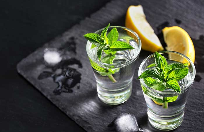 vodka with mint and ice Two glasses with a cocktail of mint and ice alcohol with lemons on the black surface